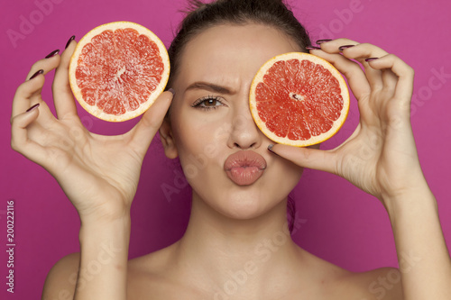 Young sexy woman posing with slices of red grapefruit on her face on pink background