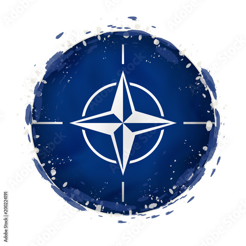 Photo  Round grunge flag of Nato with splashes in flag color.