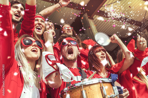 group of fans dressed in red color watching a sports event - 200224580