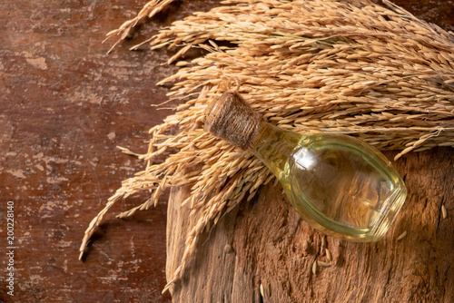 Bottle of rice bran oil and unmilled rice on wooden background Wallpaper Mural