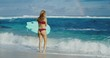 Beautiful young woman at the beach going surfing, active lifestyle