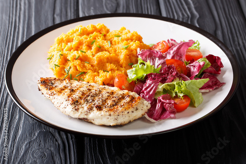 Delicious grilled chicken with garnish of sweet potato and fresh salad close-up on a plate on the table. horizontal