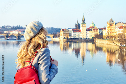 Obraz Tourist girl dicovering Prague, Czeh Republic. Charles bridge view on background. Beauty city scape - fototapety do salonu