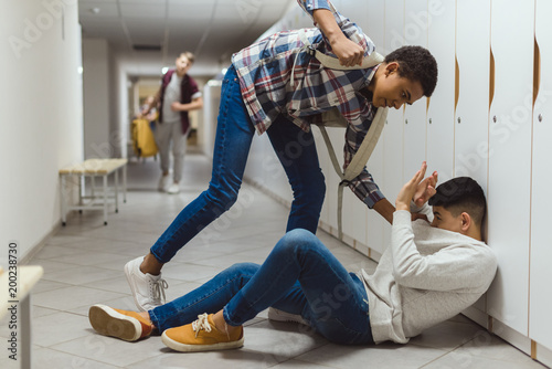 frightened schoolboy being bullied by classmate in school corridor under lockers Canvas-taulu