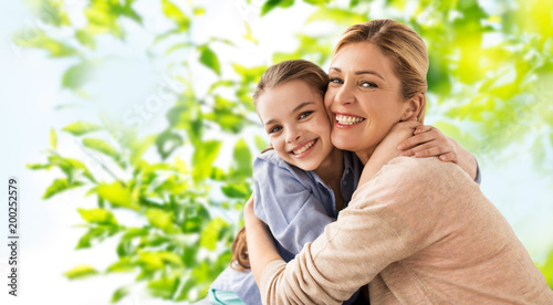 Photographie people and family concept - happy smiling mother hugging daughter over green nat