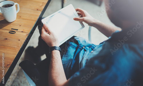 Fotografia  Closeup view of man holding digital tablet on hand and using while sitting in armchair at coworking place