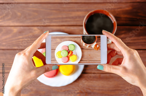 Woman taking photo of macarons dessert.