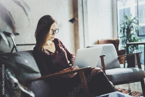 Foto  Young beautiful blonde woman sitting at the comfortable armchair and using laptop computer
