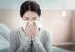 Home treatment. Ill exhausted unhappy woman sitting in the bright room holding a napkin and sneezing.