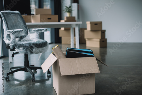 Fotografia  cardboard box with folders and office supplies in floor during relocation