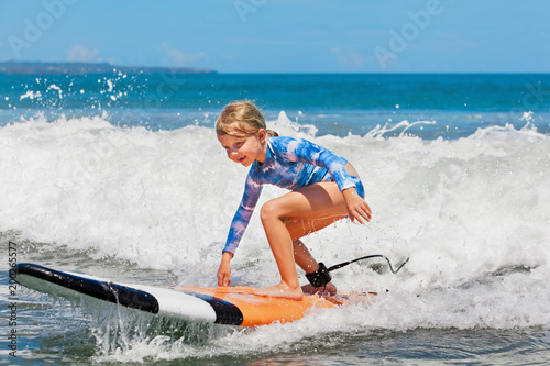 happy baby girl young surfer ride on surfboard with fun on sea