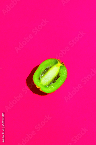 Halved Ripe Juicy Kiwi on Fuchsia Pink Background. Bright Harsh Sunlight Deep Shadow. Vibrant Neon Colors. Summer Tropical Vacation Travel Fashion Concept. Poster Banner Streamer Template