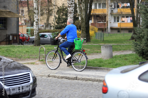 Obraz Mężczyzna na rowerze w miejskim parku z sadzonkami i konefką. - fototapety do salonu
