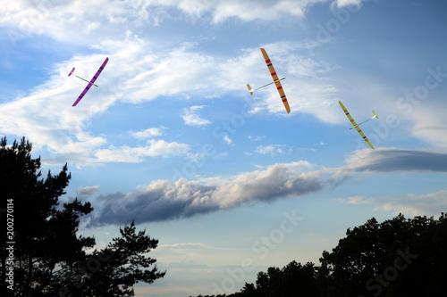 Trzy modele szybowców zdalnie sterowanych na tle błękitnego nieba.