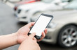 Man calls car with mobile phone APP in parking lot