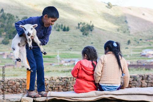 Three latin kids on the wall. Little boy holding lamb. Fototapete