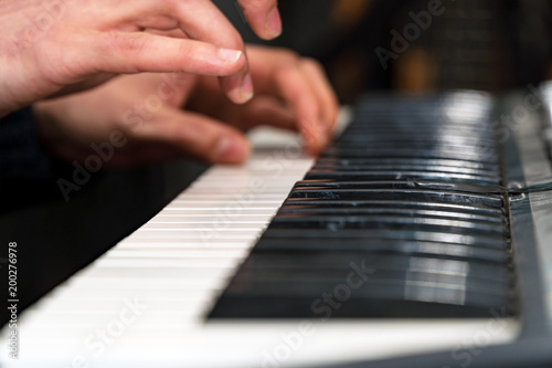 Fotografie, Obraz  Hands of a pianist close-up. Plays on the synthesizer