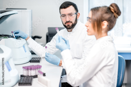 Laboratory assistants making analysis with test tubes and analyzer machines sitt Canvas Print