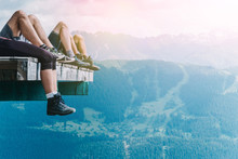 Relaxation Of Hikers In The Mountains After A Long Walk, Tourists Legs In Trekking Shoes Chilling On The Air, Copy Space