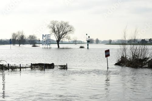 Fotografie, Obraz  een onder water gelopen voetgangersbrug in de rivier de IJssel bij Doesburg