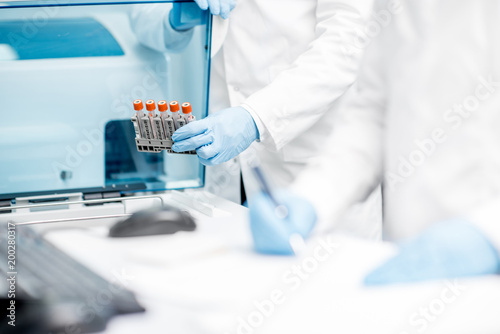 Laboratory assistant filling test tubes into the analyzer machine Canvas Print