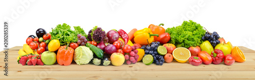 Poster Légumes frais Vegetables and fruits on wooden table boards isolated on white