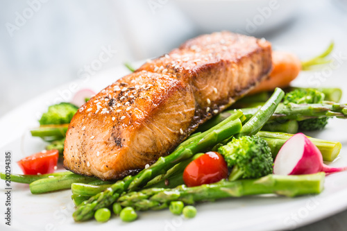 Tuinposter Vis Roasted salmon steak with asparagos broccoli carrot tomatoes radish green beans and peas. Fish meal with fresh vegetable
