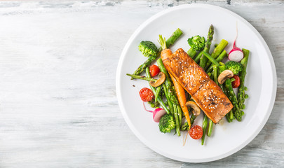 Fototapeta Roasted salmon steak with asparagos broccoli carrot tomatoes radish green beans and peas. Fish meal with fresh vegetable
