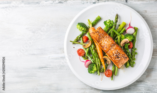 Poster Kruidenierswinkel Roasted salmon steak with asparagos broccoli carrot tomatoes radish green beans and peas. Fish meal with fresh vegetable