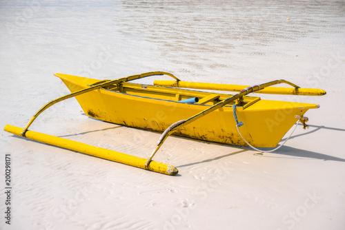 Small yellow bangka boat on the sandy beach, Philippines