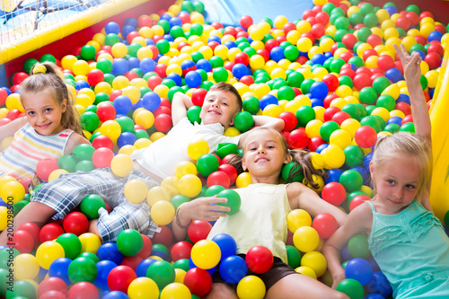 kids playing with multicolored plastic balls .