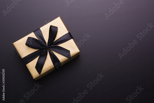 Fotografía Hands holding wrapped gift box with colored ribbon as a present for Christmas, new year, mother's day, anniversary, birthday, party, on black background, top view