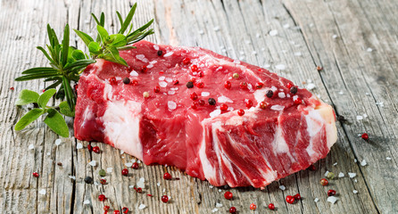 Fototapeta Raw Entrecote Beefsteak With Rosemary pepper On Wooden Table