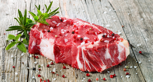 Photo Stands Meat Raw Entrecote Beefsteak With Rosemary pepper On Wooden Table