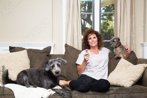 Cuadros en Lienzo Adult Female Watching TV With Dogs on Sofa