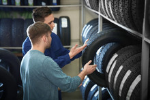 Service Center Consultant Helping Customer To Choose Tire In Store