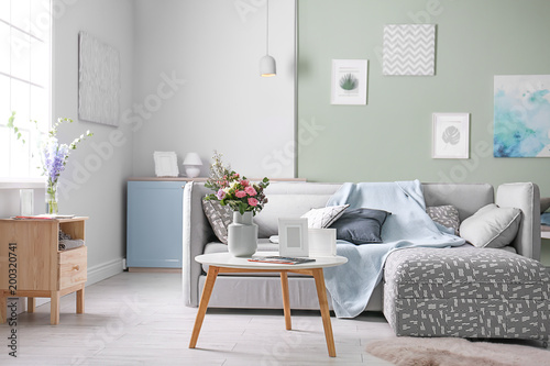 Valokuva  Cozy living room interior with comfortable sofa and elegant table