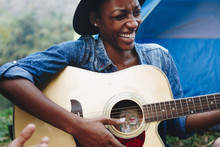 African American Woman Playing A Guitar At A Campsite