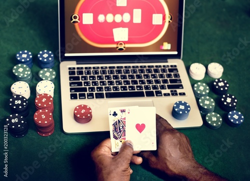 фотография  Hand holding card playing online gambling