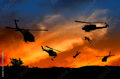 Tuinposter Helicopter Silhouette Soldiers rappel down to attack from helicopter with sunset and copy space add text ( Concept stop hostilities To peace)