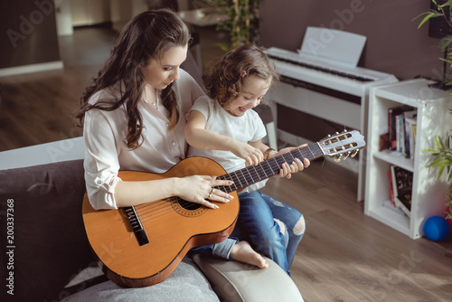 Papiers peints Artiste KB Mother and daughter playing a guitar