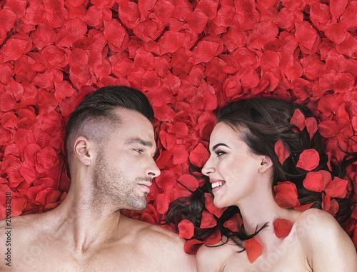 Papiers peints Artiste KB Romantic couple laying on rose petals