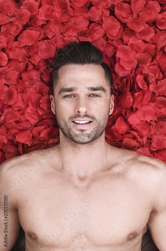Papiers peints Artiste KB Handsome man laying on rose petals