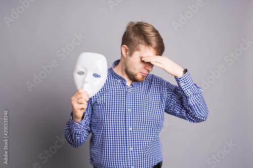 Fotografie, Tablou  Sad man taking off plain white mask revealing face, gray background