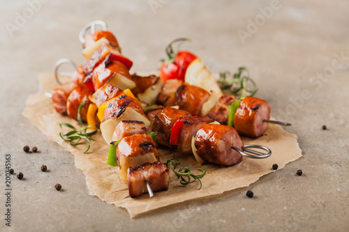 Fotografía  Grilled skewers with sausage, bacon and vegetables.