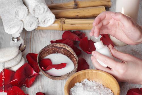 Zdjęcie XXL Zabiegi spa dla dłoni z płatkami czerwonych róż i akcesoriów, stosując balsam do zmiękczania skóry