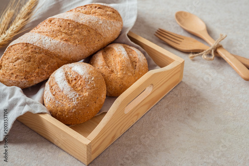 Foto op Canvas Brood Bread and buns on wooden tray .