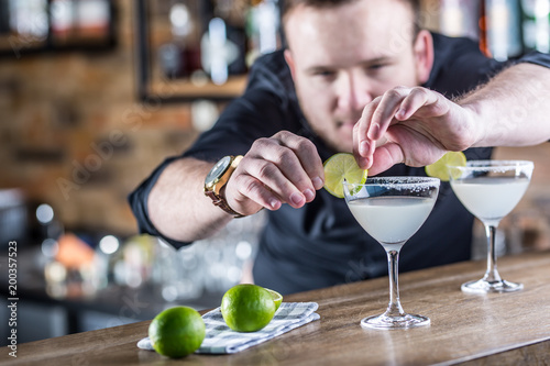 Fotografía  Barman in pub or restaurant  preparing a cocktail drink margarita