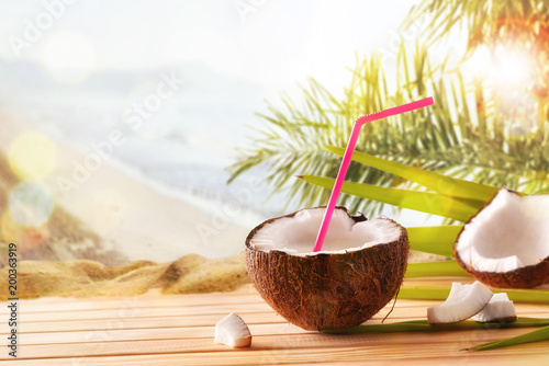 Coconut drink in coconut fruit on table at tropical beach