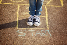 Closeup Of Boy's Legs And Playing Hopscotch On Playground Outdoors. Hopscotch Popular Street Game